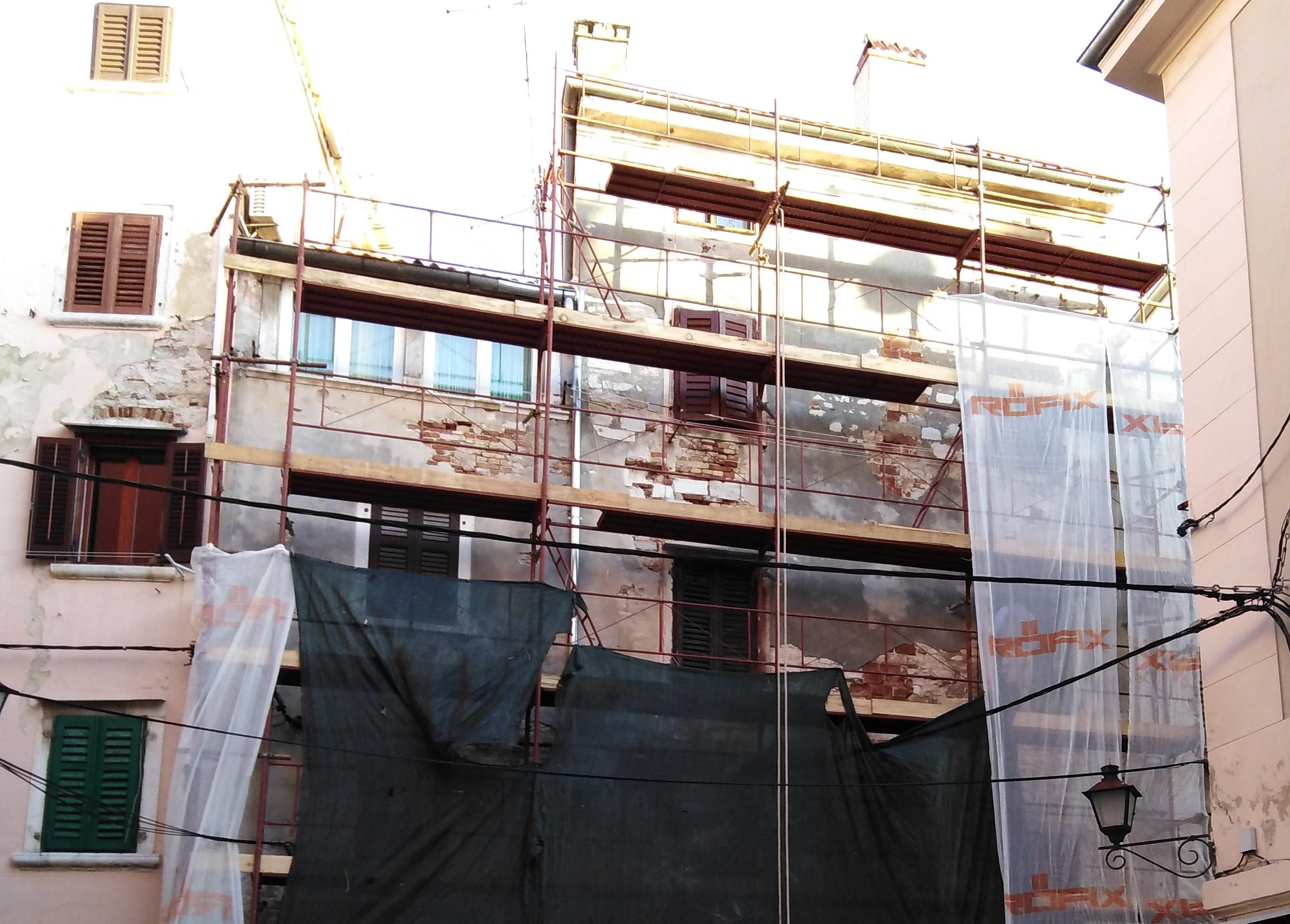 Il tetto e la facciata dell'edificio in via Arsenale 1 in fase di ristrutturazione